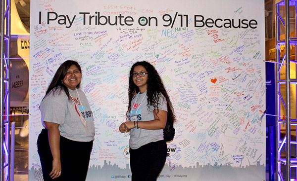 APPLE Corps' Doménica Ramírez-Pérez '18 and Rosalma Pineda '21 sign the 9/11 Tribute Wall