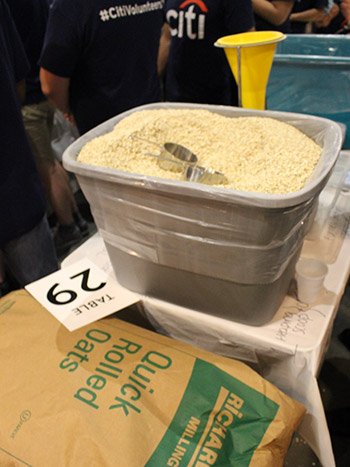 Volunteers measure oatmeal for families in need