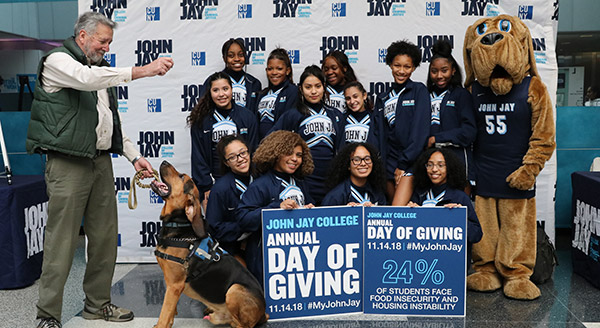 The John Jay Cheerleading Squad with two excited bloodhounds