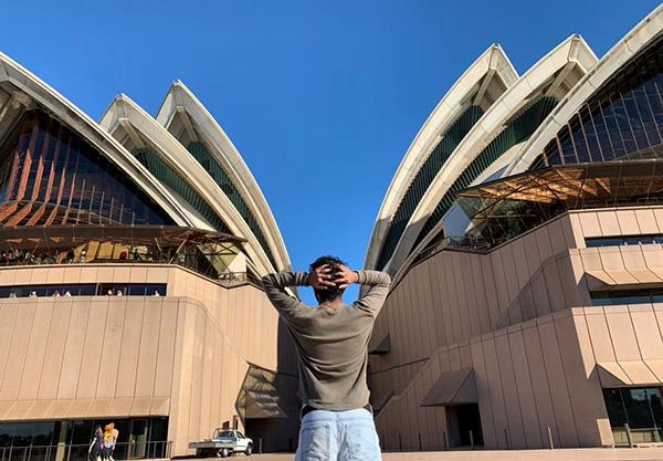 Bikram standing in front of the Sydney Opera House.