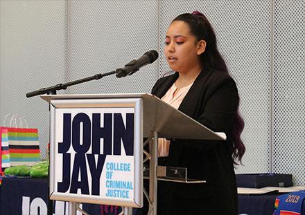 A student telling the audience about her experience with the ¡Adelante! program