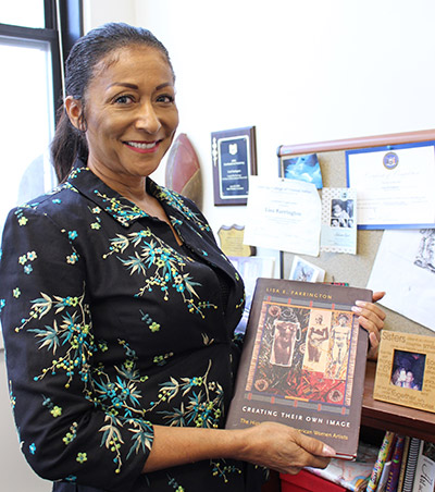 Farrington holding up one of her books, Creating Their Own Image: The History of African-American Women Artists