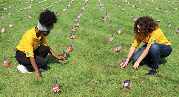 Helly Florian '20 and Rosmary Reyes '20 help plant flags on the Jay Walk.