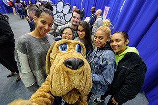 John Jay Bloodhound taking a selfie with students at John Jay Homecoming