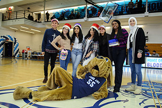 John Jay Bloodhound posing with students