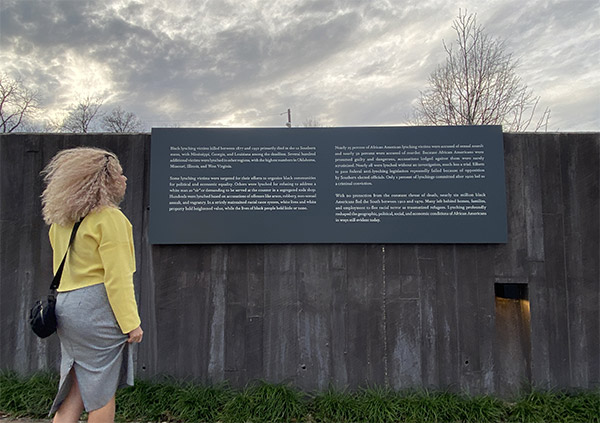 Salmanova, at the National Memorial for Peace and Justice,  reading about lynching victims in black communities