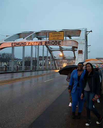 Johnson (in blue) walking on the Edmund Pettus Bridge