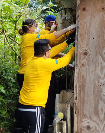 The team works to remove the damaged pieces of the wall