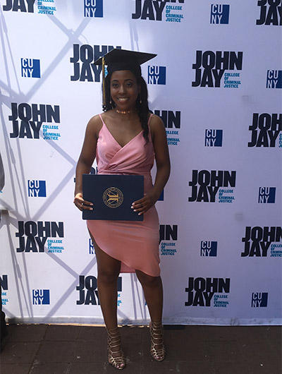 Roberts holds up her degree from John Jay