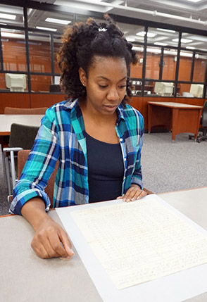 Valencia McMillan, an MPA graduate _Forensic Accounting, examines a 200-year old invoice for the care of enslaved children, in the records of the Comptroller's Office at the NY State Archive