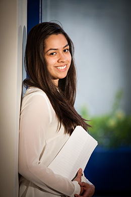 Student holding a book leaning on a wall