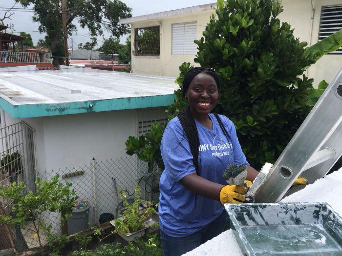 Alexis Augustine, ayudando a arreglar el techo de una casa