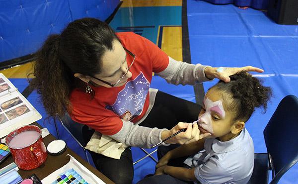 Laura DeVries, Senior Designer, meticulously paints a child's face.