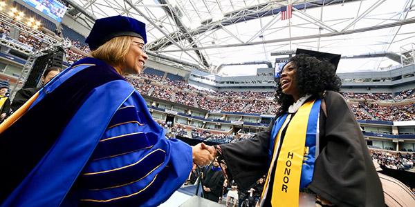 President Karol Mason shaking hand with John Jay graduate