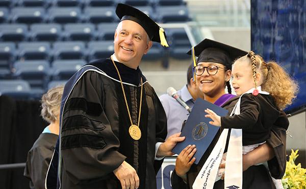 CUNY Chancellor, Félix V. Matos Rodríguez poses with a John Jay graduate