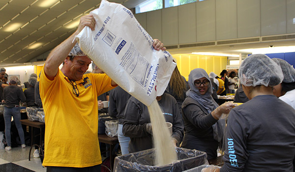 Director of COSL, Declan Walsh refills the rice supply