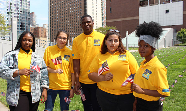 (left to right) Students Kenya Thomas '22, Emine Kilic '19, Abdourahamane Ly '19, Jennifer Hurtado '20, and Helly Forian '20 helped plant flags on the Jay Walk.