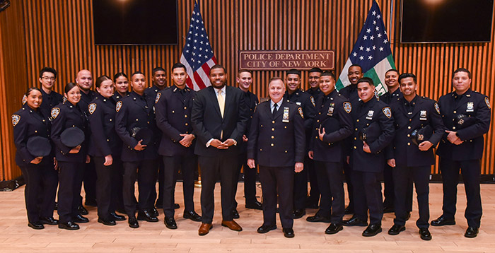 Adjunct Professor Alden Foster '12 and Adjunct Professor John Benoit (both at center)  with 18 former John Jay Students, now police officers, during their visit to One Police Plaza