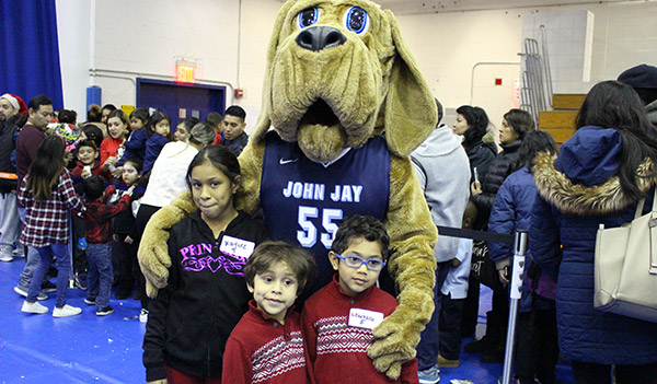 Bloodhound posing with kids at the John Jay Annual Children's Holiday Party