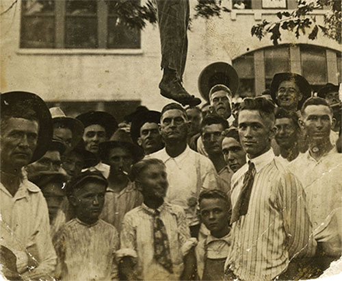 White men and boys pose beneath the body of Lige Daniels, a black man, shortly after he was lynched on August 3, 1920, in Center, Texas