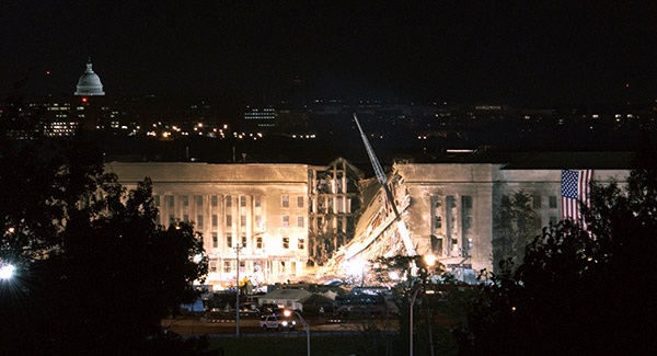 Caption:  An American flag draped to right of the damaged area of the Pentagon on the night of September 12, 2001