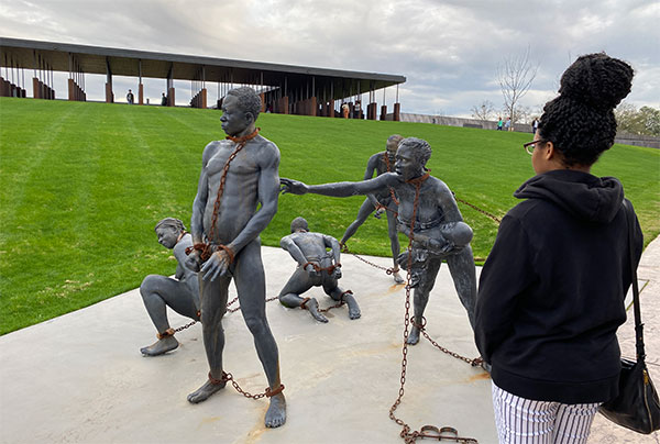Nairne standing in front of artist Kwame Akoto-Bamfo's sculpture on slavery at the National Memorial for Peace and Justice