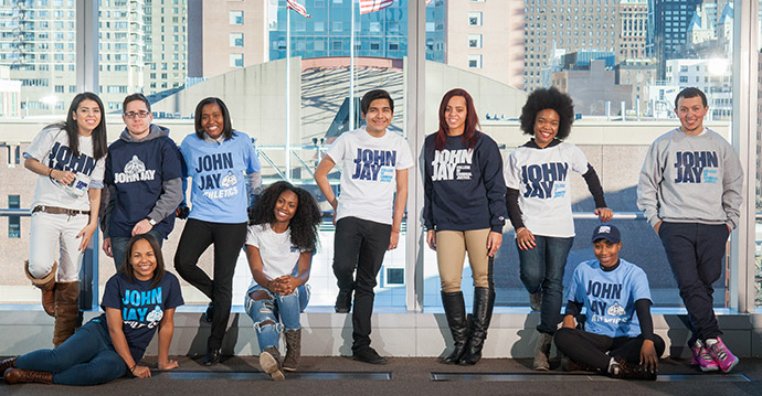 A group of diverse John Jay students in front of window
