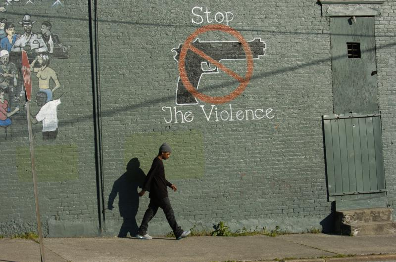 Man waking by wall with a Stop the Violence sign